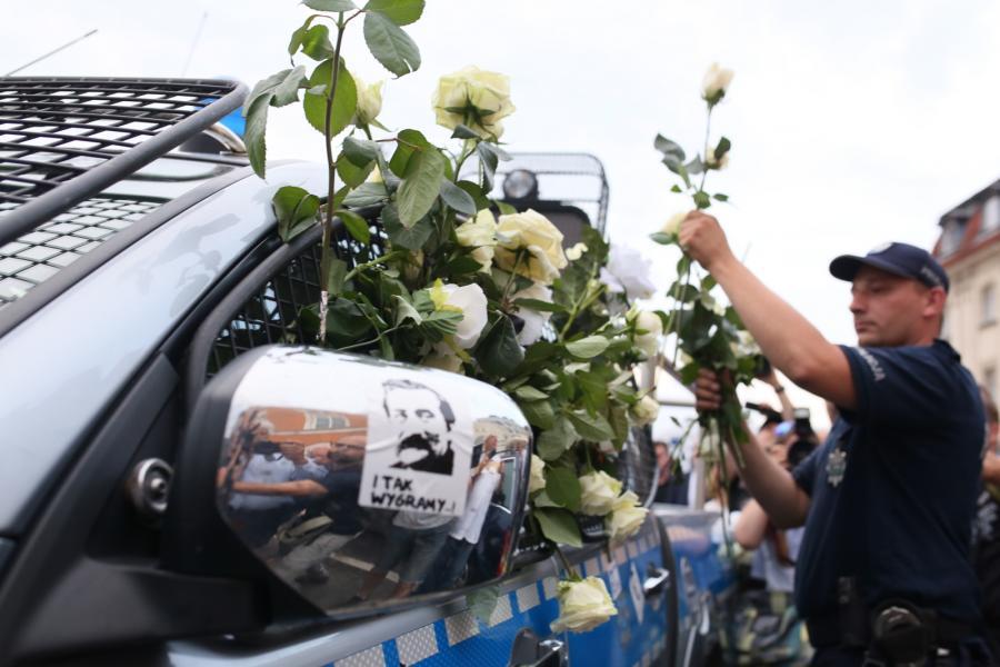 Uczestnicy kontrmanifestacji opuścili pl. Zamkowy, zostawiając białe róże zatknięte za osłony zabezpieczające szyby radiowozu policyjnego