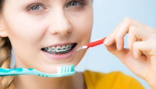 Kobieta myje zęby w aparacie ortodontycznym