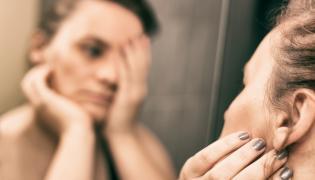 Smutna kobieta przed lustrem