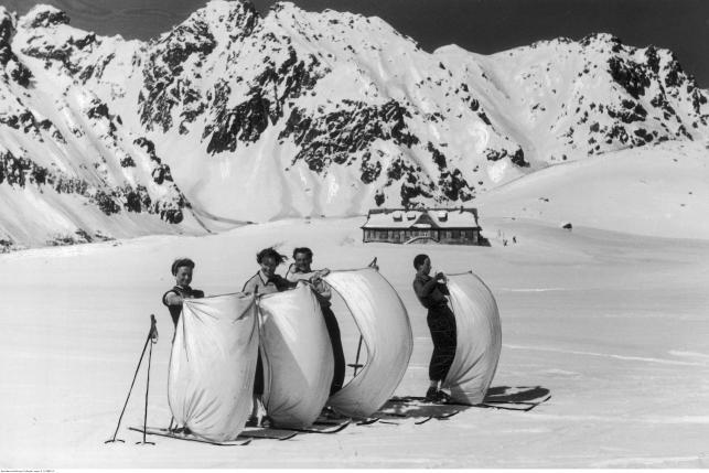 Narciarze podczas jazdy na nartach z przytwierdzonym żaglem na zamarzniętym jeziorze