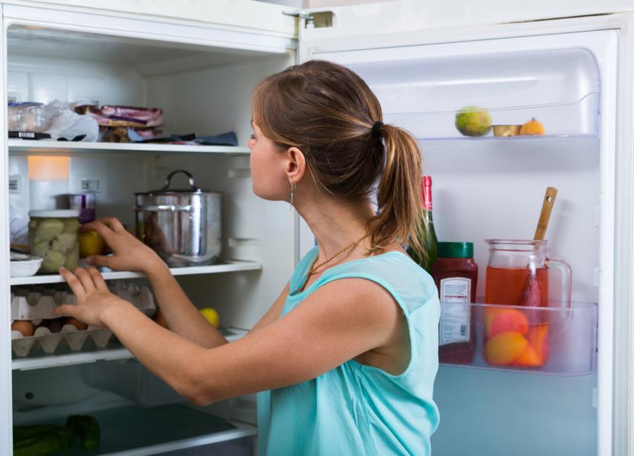 Kobieta stoi przy lodówce