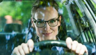 Kobieta w okularach prowadzi samochód