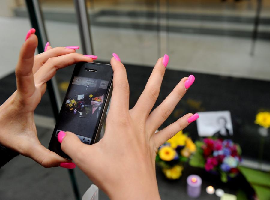 Kobieta fotografuje swym iPhonem kwiaty złożone na George Street w Sydney