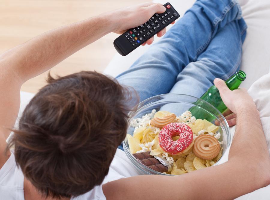 Mężczyzna je przekąski podczas oglądania TV