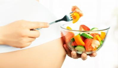 Kobieta w ciąży je sałatkę
