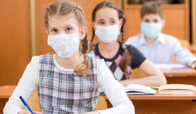 Dzieci na lekcji siedzą w maseczkach na twarzy