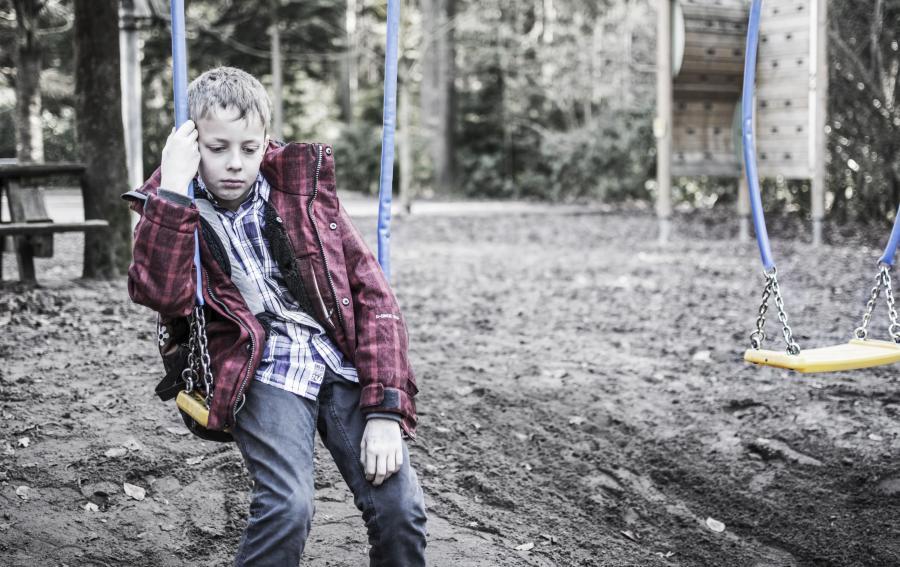 Smutny chłopiec na huśtawce