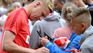 Kamil Glik (L) rozdaje autografy przed treningiem kadry na boisku w ośrodku wypoczynkowym w Arłamowie