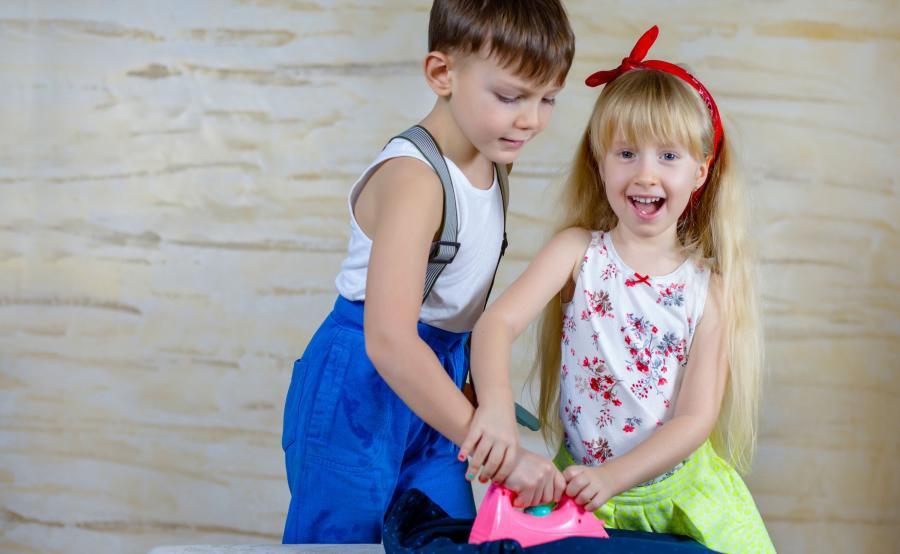 Chłopiec z dziewczynką bawią się żelazkiem