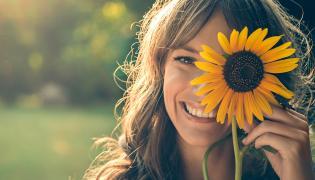 Kobieta zasłanie oko słonecznikiem